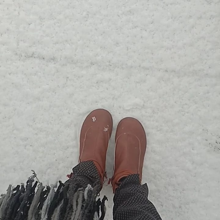 A woman's Brown leather boots on the fluffy white snow floor