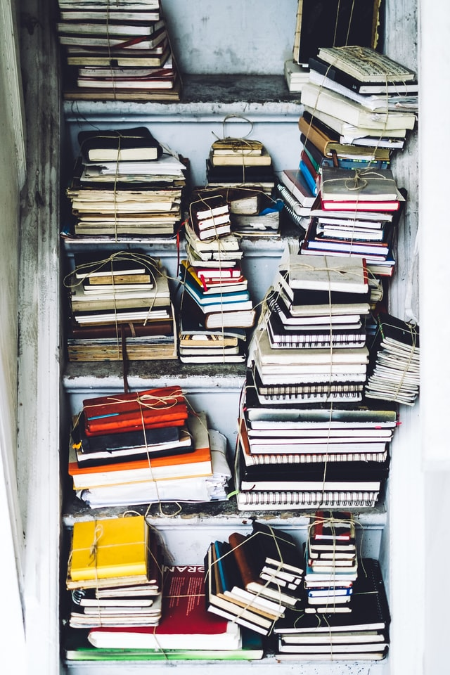 Lot of books arranged in a big shelf, good photo for a decluttering challenge