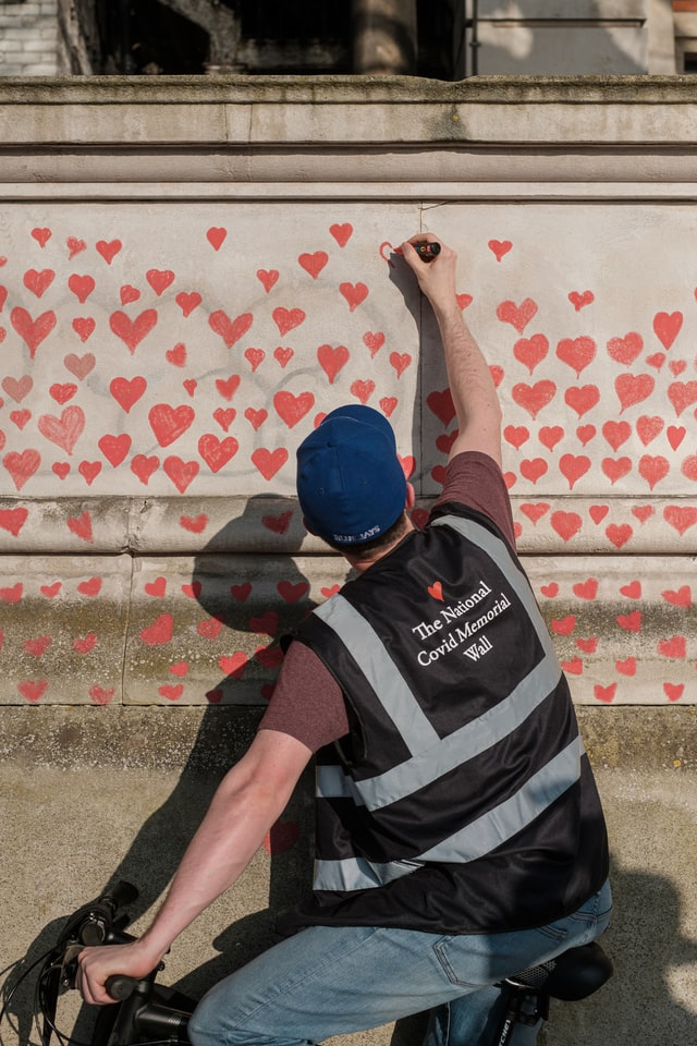 A man in a bicycle drawing a heart in the Wall of hearts near St. Thomas hospital, London. Using this unsplash image for Have you vaccinated post in Jayanthy's free space.