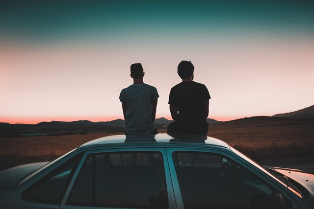 Two men sitting on the roof of a car watching the sunset. Picture used for a tale of two brothers in Jayanthy's Free Space.